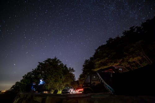 Vehicles Parked Near A Cliff Under A Starry Sky
