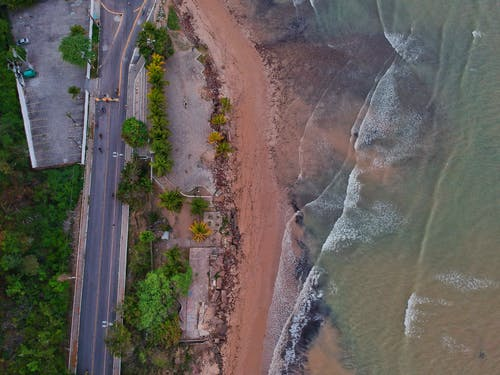 Aerial View of Waves Moving Towards Shore near Road