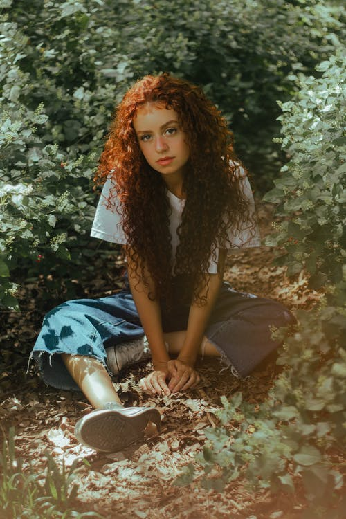 Woman with Curly Hair Sitting Down on Ground Near Green Leafed Plants