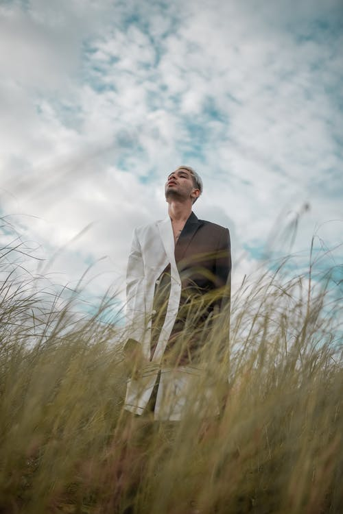 Man Wearing a black and White Suit In A Grassy Area