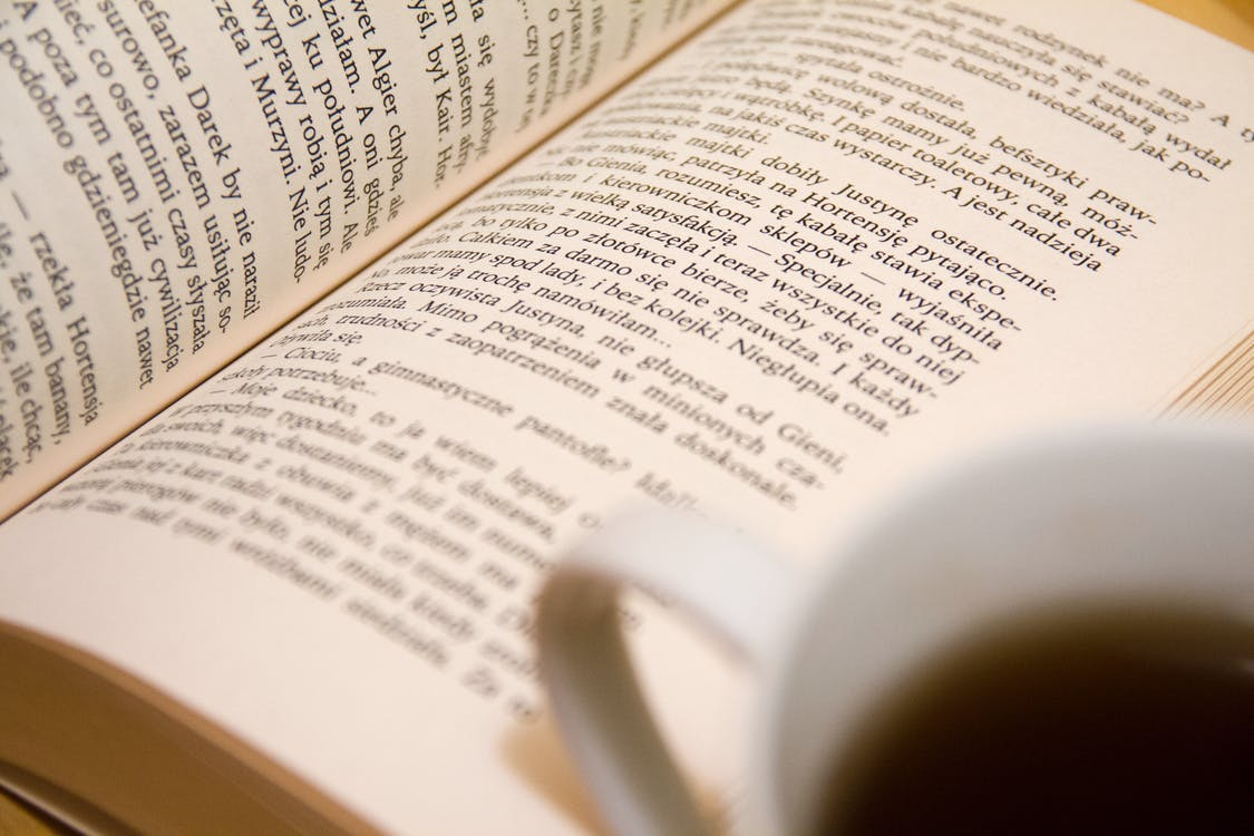 Bookpage Near the White Ceramic Mug
