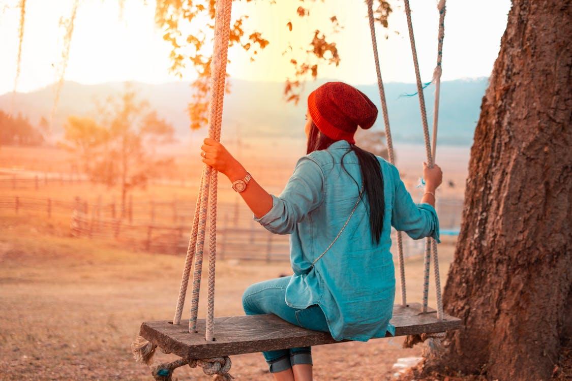 Woman Sitting on Swing Beside Tree