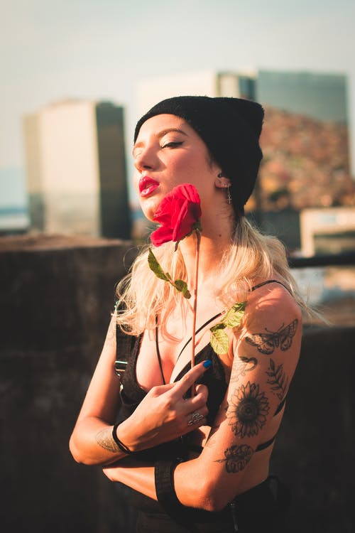Selective Focus Photo of Tattooed Woman in Black Outfit and Beanie Hat Holding Red Flower