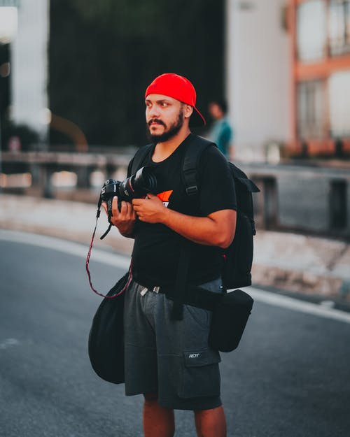 Man Wearing Black  T-Shirt and Red Cap Holding Camera