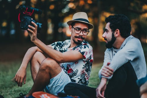 Man Holding Camera Beside Another Man