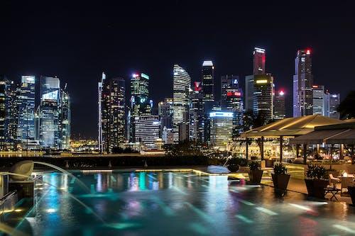 akşam, aydınlatılmış, binalar, boş zaman içeren Ücretsiz stok fotoğraf