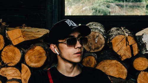 Close-Up Photo Of Man Near Wooden Logs
