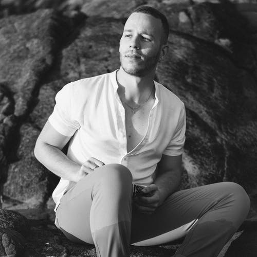 Monochrome Photography Of Man Sitting On Rock