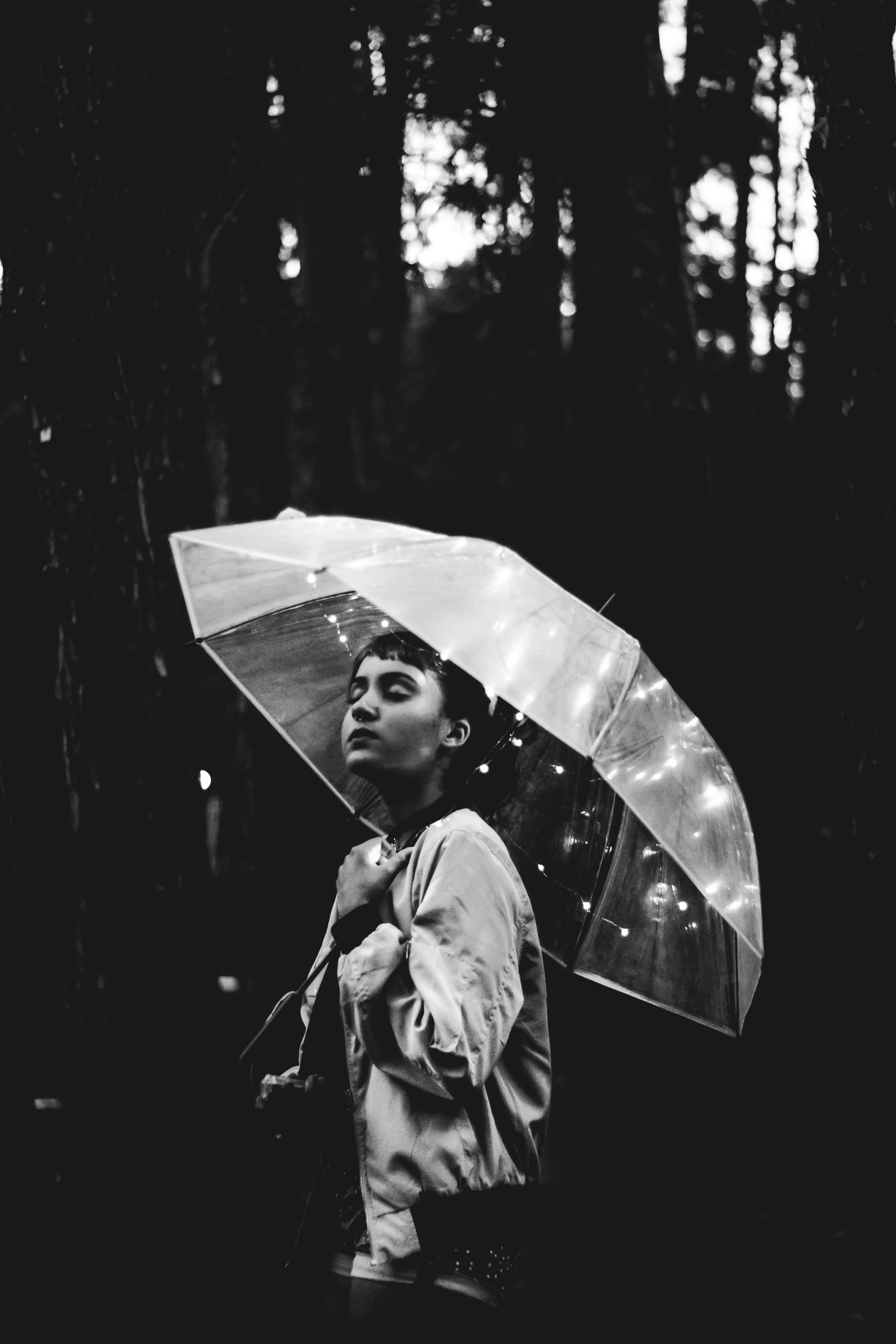 Grayscale Image of Woman Walking Through the Rain While Holding Umbrella