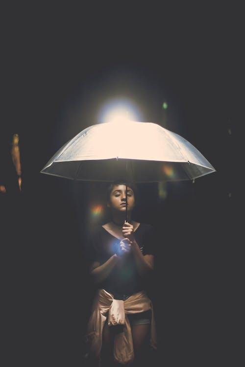 Woman Holding Illuminated Lamp at Night