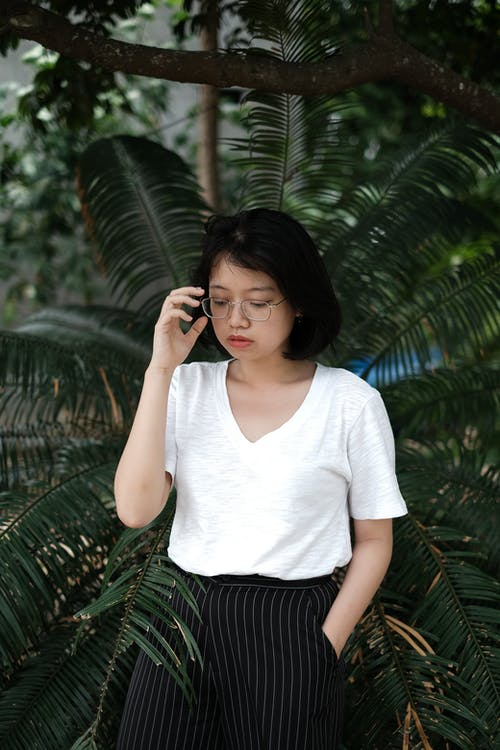 Photo Of Woman Standing Behind Palm Plant