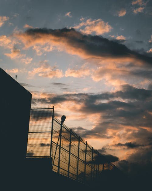 akşam karanlığı, altın saat, bulutlu gökyüzü, çit içeren Ücretsiz stok fotoğraf