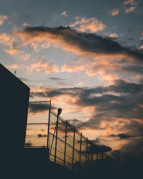 Fotobanka sbezplatnými fotkami na tému dramatická obloha, magická hodina, obloha pokrytá oblakmi, ohrada