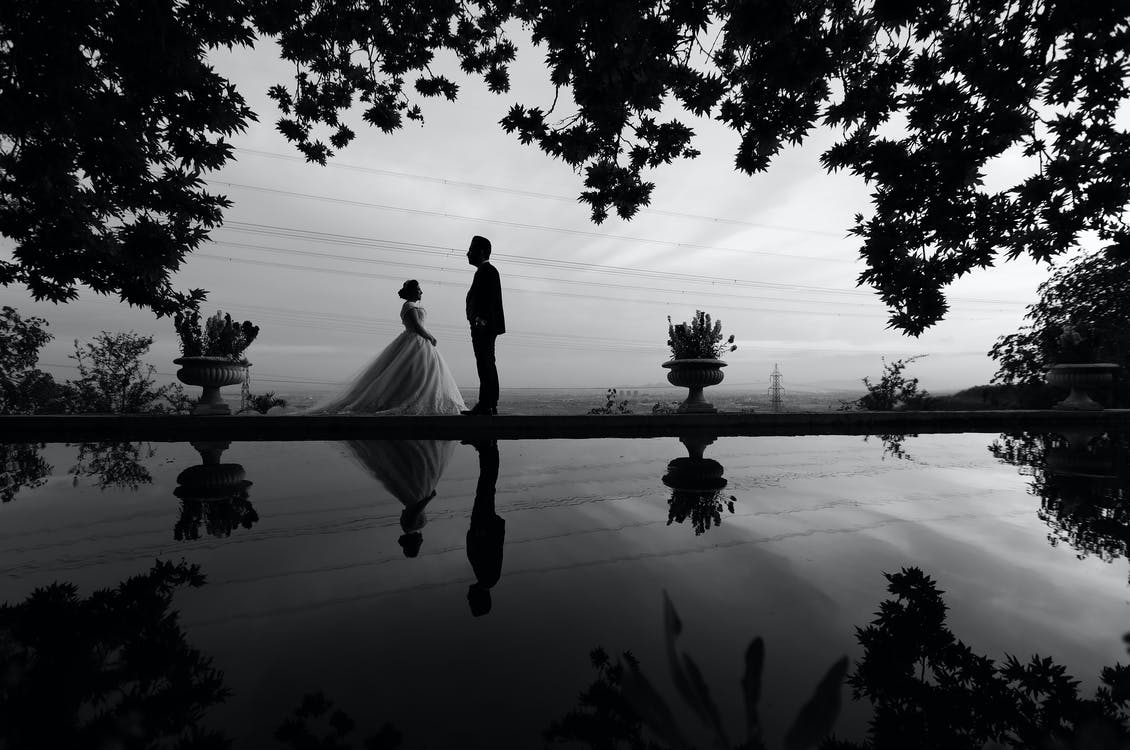 Grayscale Photo of Bride and Groom Facing Each Other Standing by Body of Water