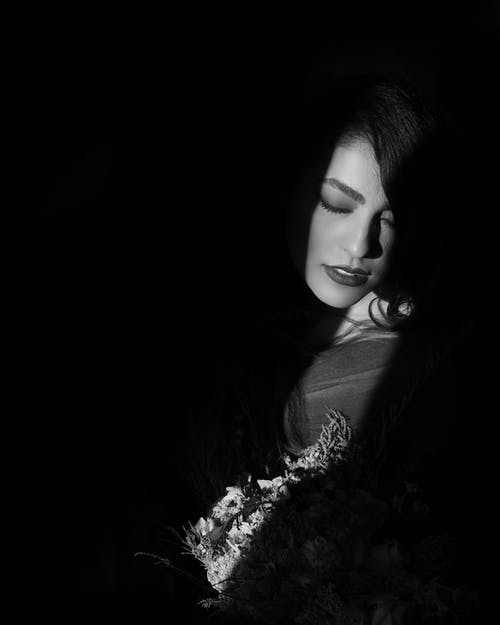 Light and Shadow Photo of Woman Inside Dark Room Posing With Her Eyes Closed While Holding a Bouquet of Flowers