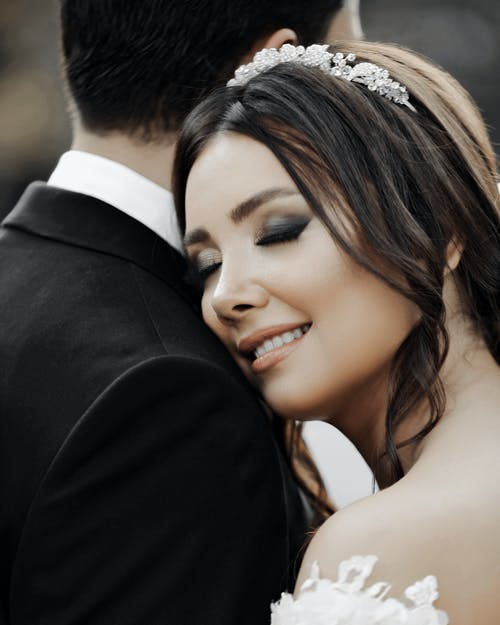 Close-up of Smiling Bride With Her Eyes Closed Hugging Groom