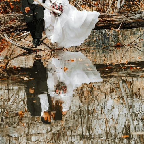 Bride and Groom Sitting on Fallen Tree Above Body of Water