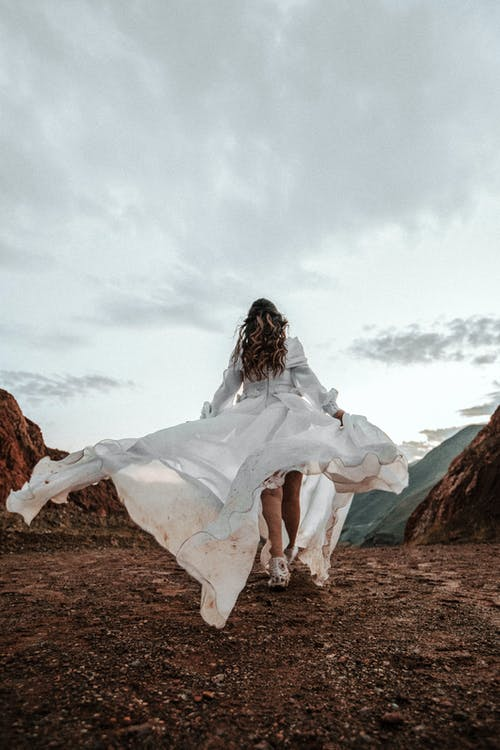 Back View Photo of Woman in White Dress Walking on Muddy Path