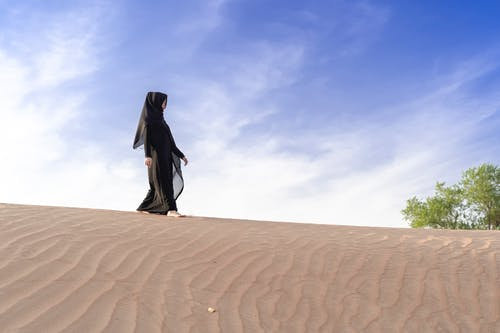 Photo of Woman Wearing Abaya While Walking on Desert