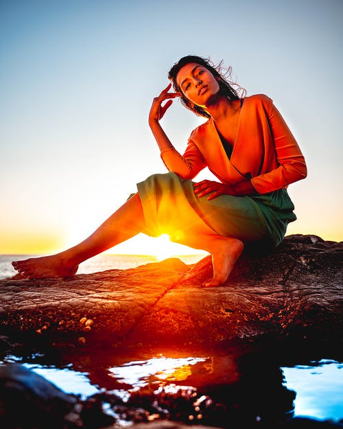 Woman Sitting on Rock During Golden Hour
