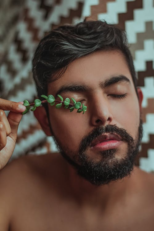 A Man Holds A`Succulent Leaf Over His Closed Eye