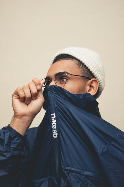 Close up photo of man in beanie hat and glasses covering his mouth with his blue jacket