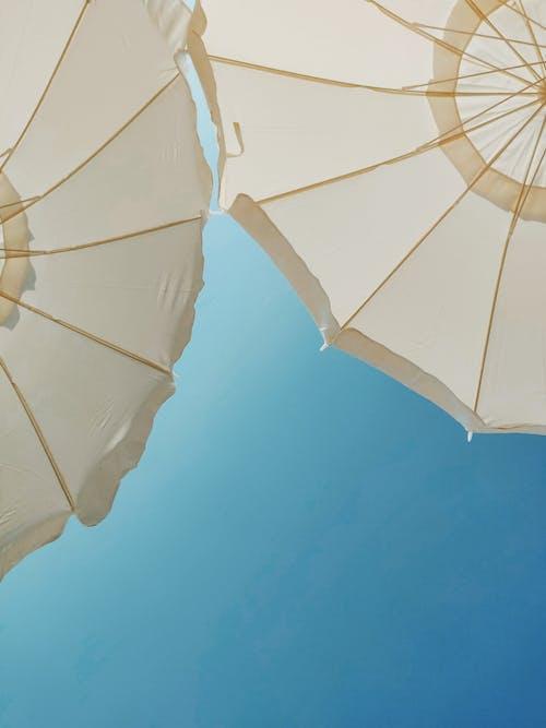 Low-Angle Photo of White Patio Umbrellas