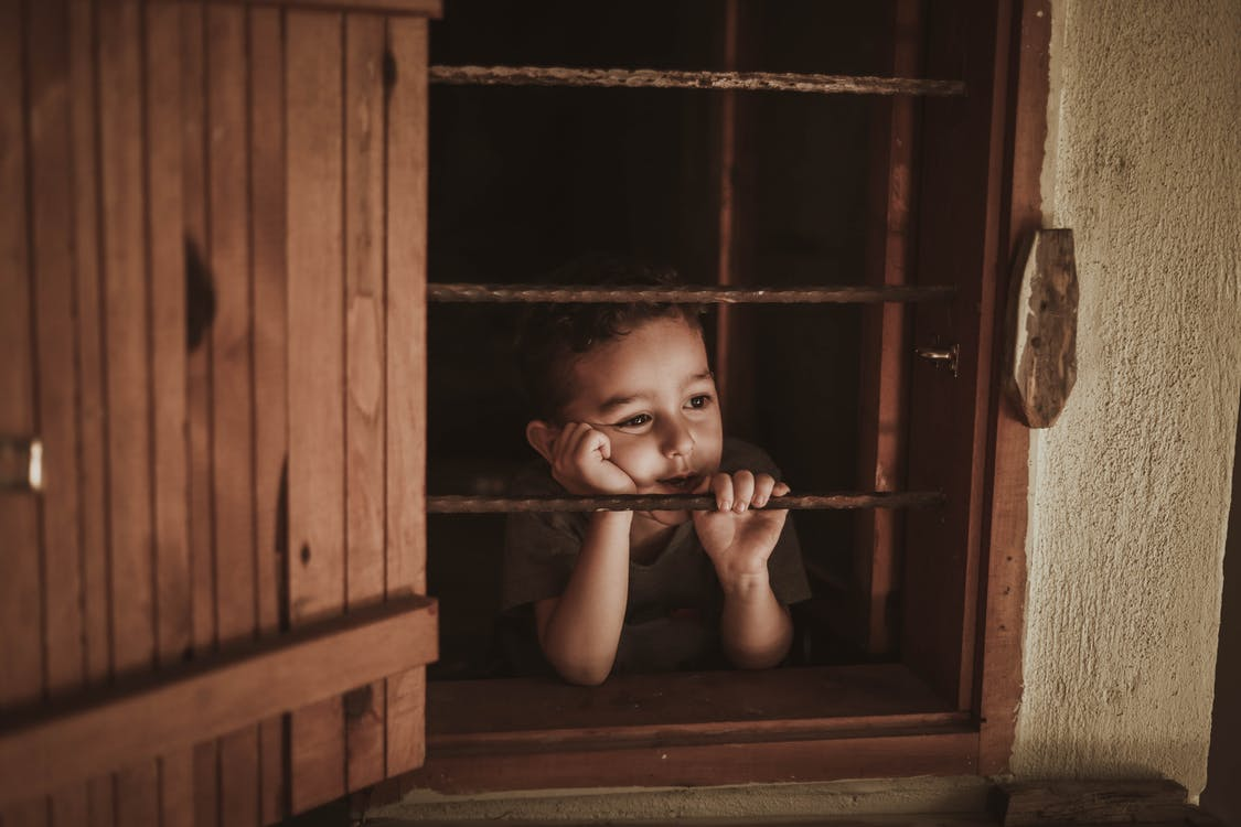 Photo Of Boy Leaning On Window Rails