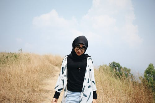 Photo of Woman in Black Hijab Walking Alone on Dirt Road