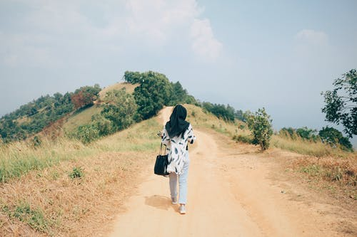 Back View Photo Woman in Black Hijab Walking Alone on Dirt Road