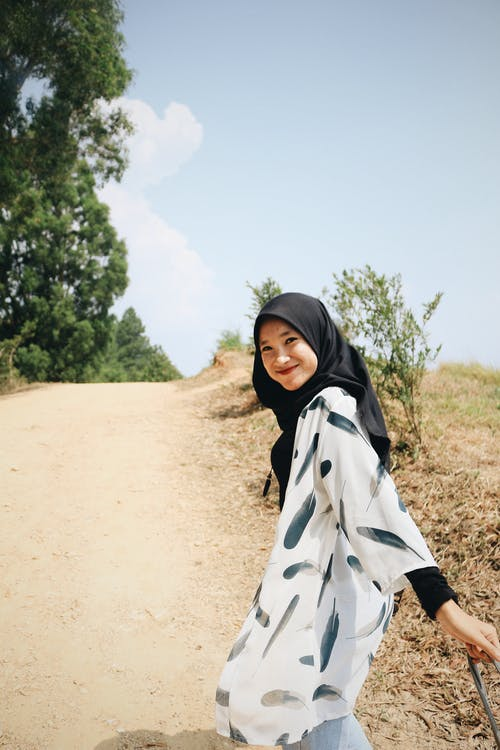 Photo of Smiling Woman in Black Hijab on Dirt Road Looking Back