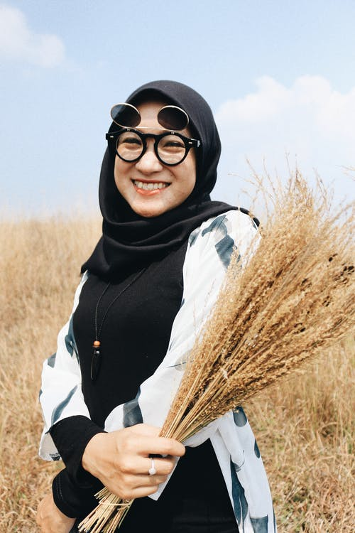 Playful woman with heap of wheat in rural field