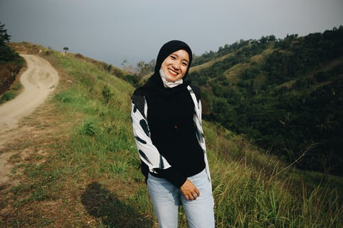 Photo of Smiling Woman in Black Hijab Posing by Dirt Road
