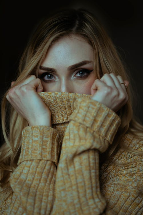 Close-up Photo of Woman Covering Her Mouth with a Brown Sweater