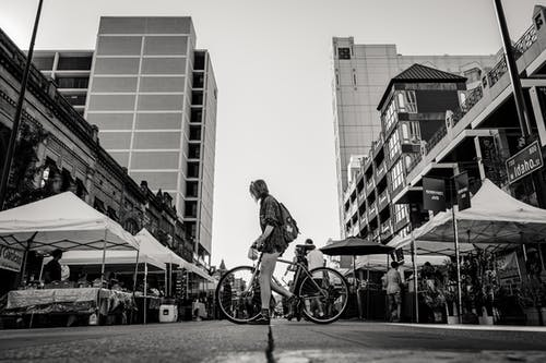Monochrome Photo of Person Holding Bike