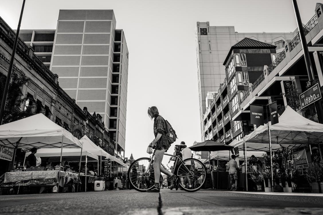 Monochrome Photo of Person Holding Bike