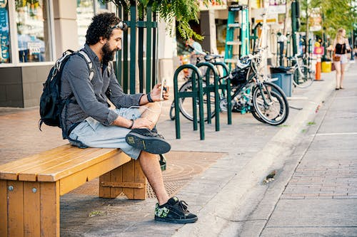 Man Sitting on Brown Wooden Bench Using His Smartphone