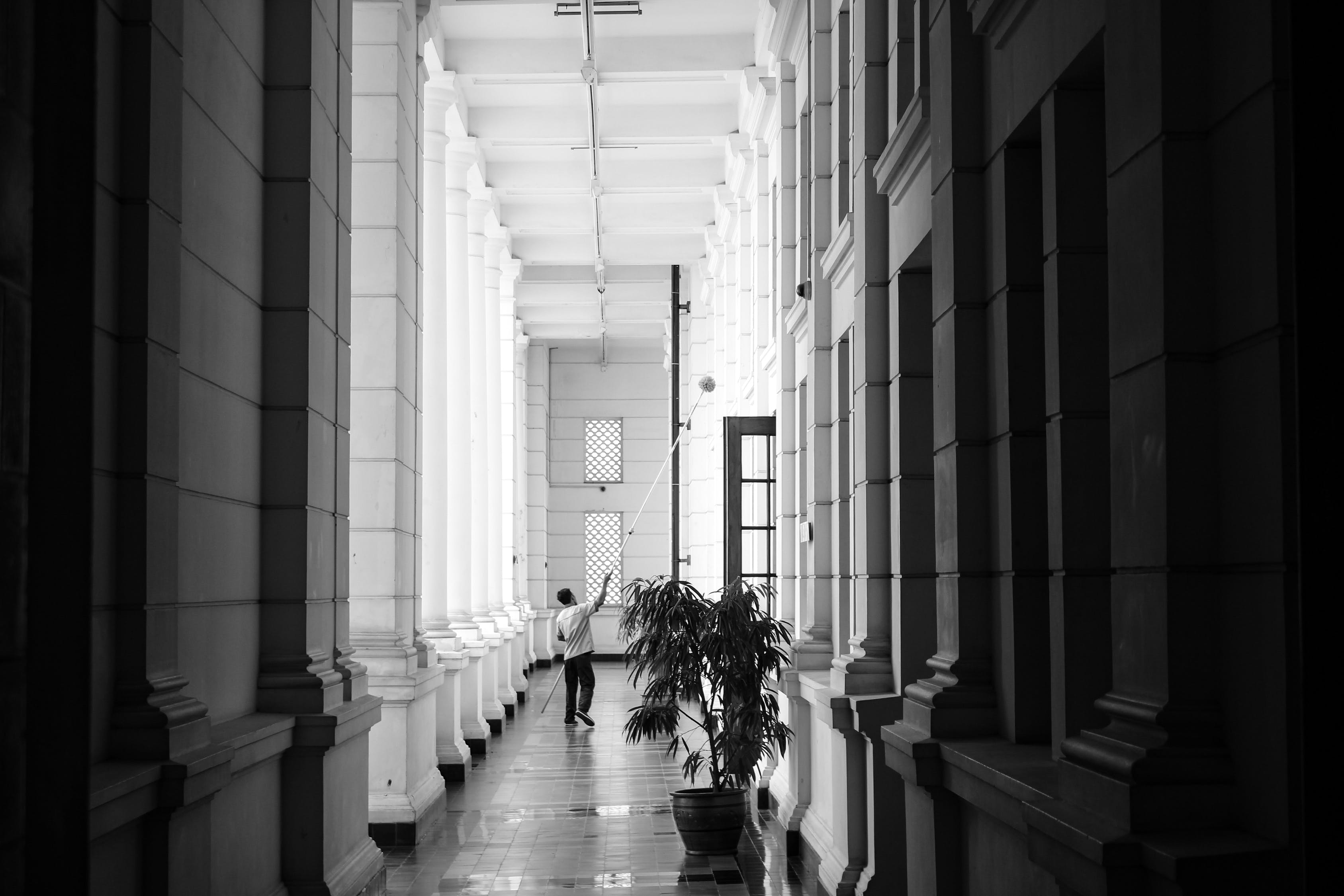Grayscale Photo of Person Walking on Corridor