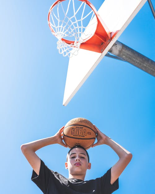 Boy Holding a Basket Ball On His Head