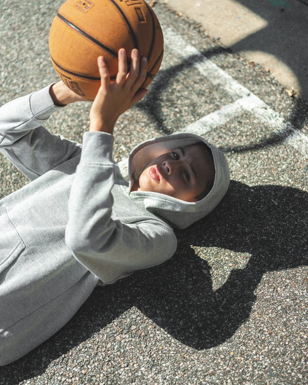 A Boy In A Hoodie Lying On The Floor With A Basketball In Hand