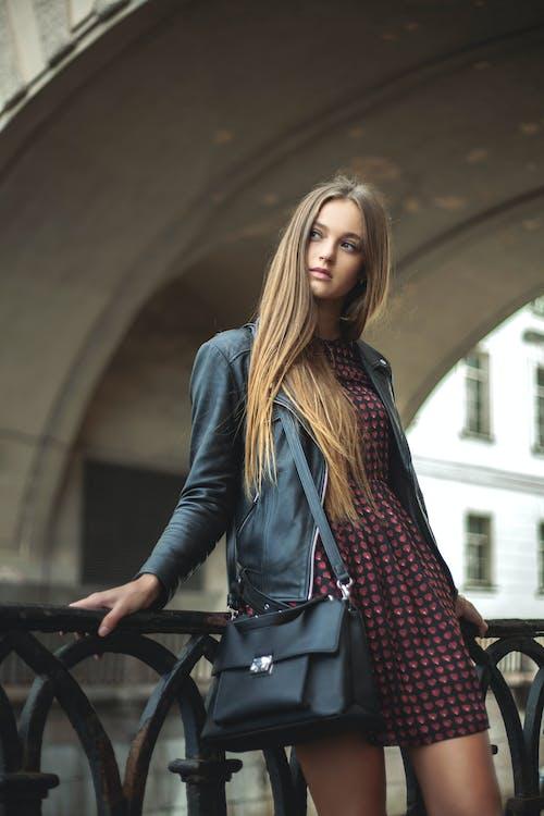 Woman Wearing Black Full-zip Leather Jacket Leaning on Black Metal Fence