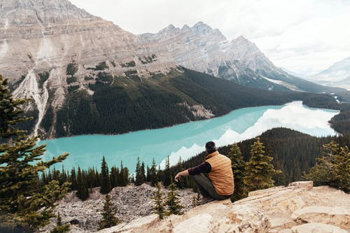 Man Wearing Brown Vest Sitting on Mountain Looking at Lake
