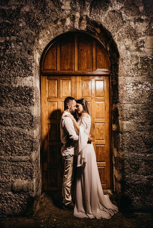 Bride And Groom Kissing Gesture In Front Of A Wooden Door