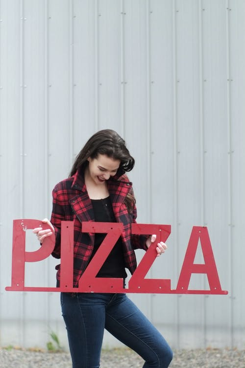 A Woman Holding A Red Pizza Signboard