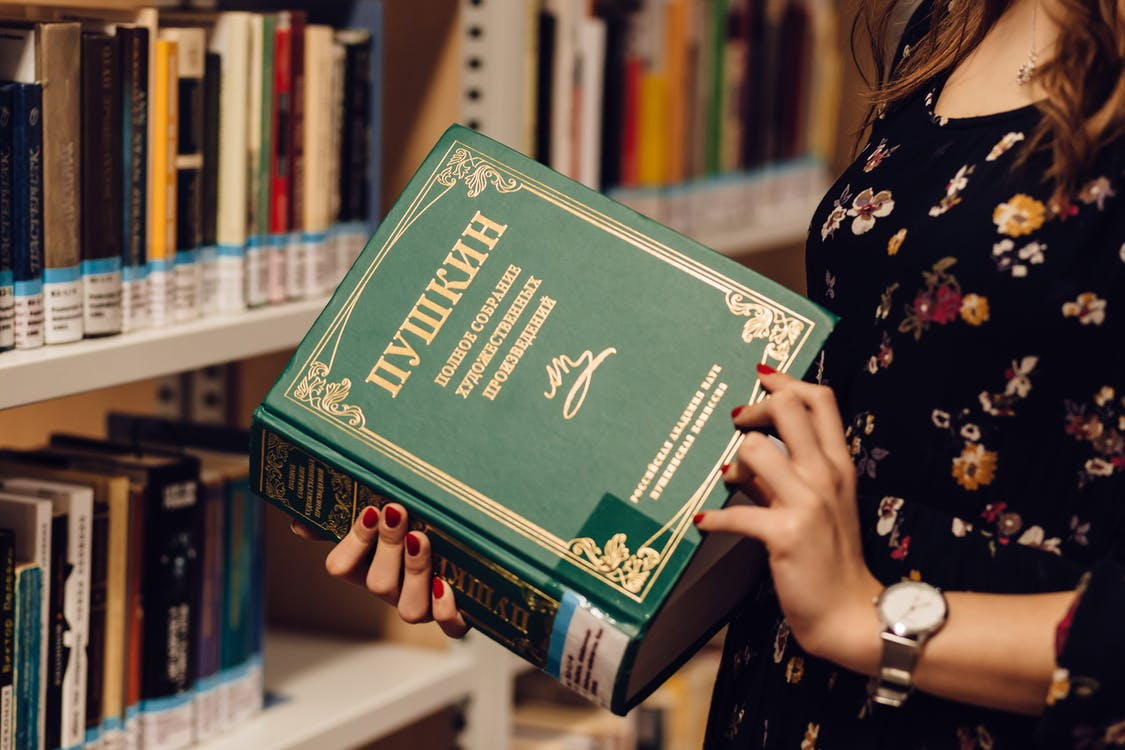 Woman Opening Book in Front of Bookshelf