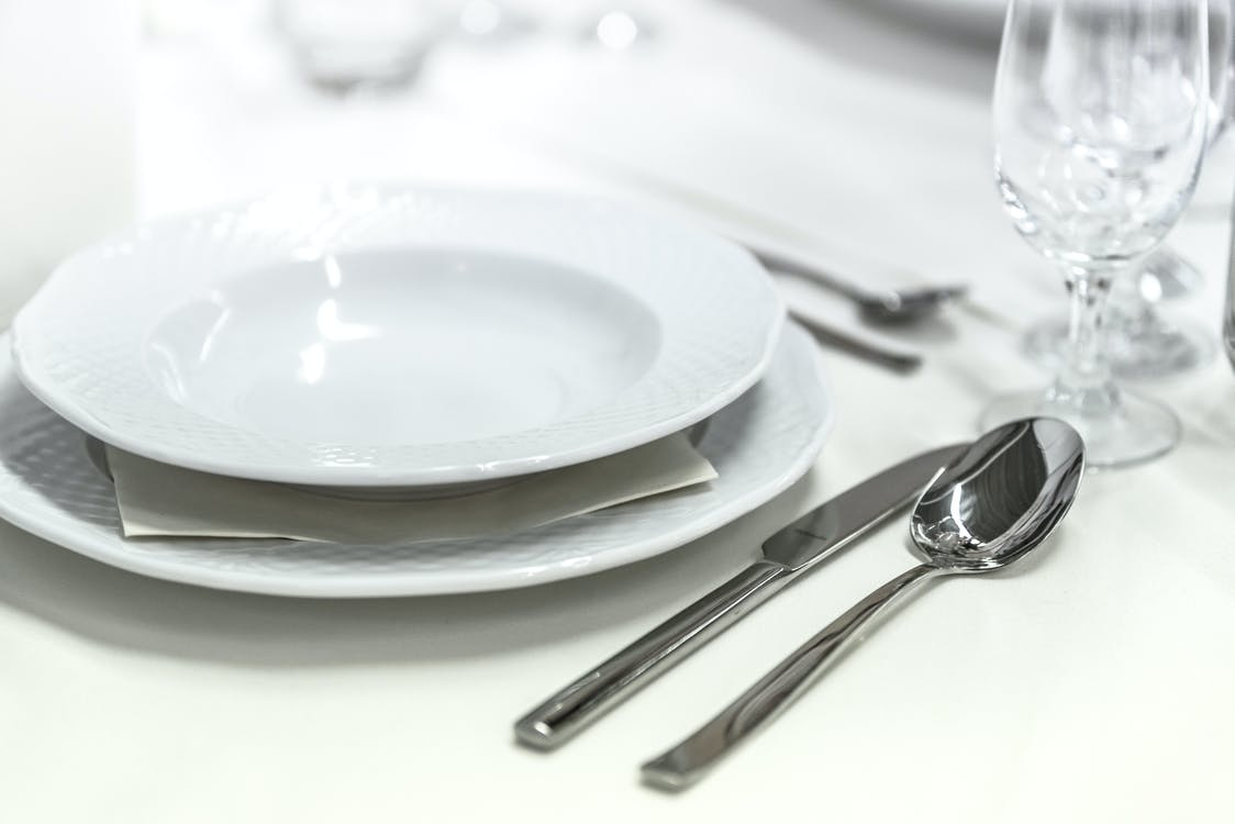 Round White Ceramic Bowl Placed on Table Beside Wine Glass