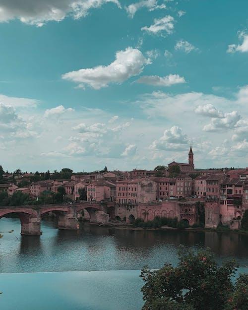 River Beside Concrete Bridge and Buildings