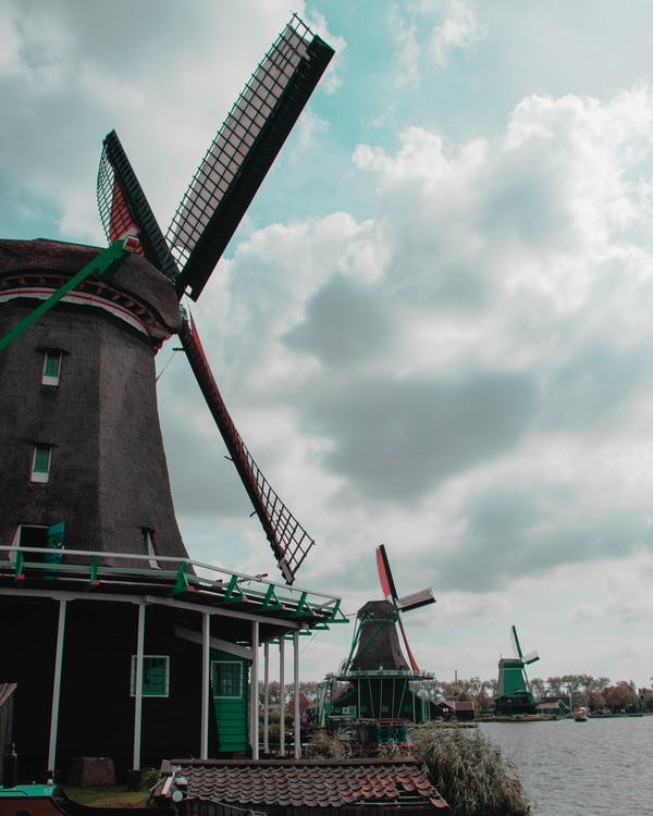 Windmills Beside Body Of Water Under Cloudy Sky