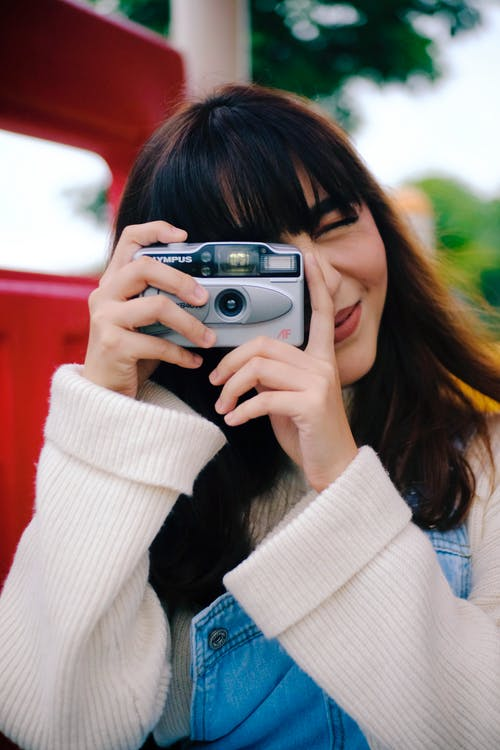 Woman Wearing White Sweater Using Camera