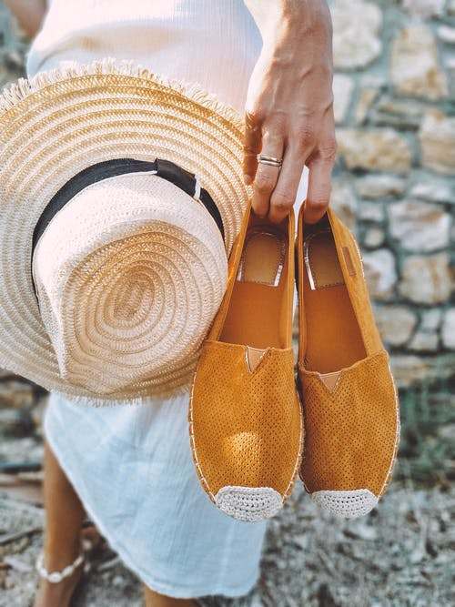 Selective Focus Photography of Woman Holding Brown Espadrille Shoes and Brown Sun Hat